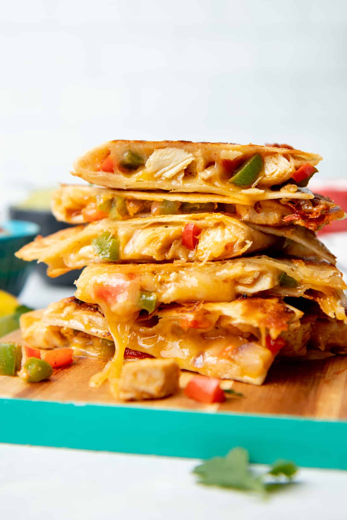 Chicken quesadillas are stacked on a wooden cutting board. The board has a teal edge.