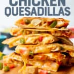 "Chicken quesadillas are stacked on top of a wooden cutting board. Text overlay reads, ""The best ever! Chicken Quesadillas."""