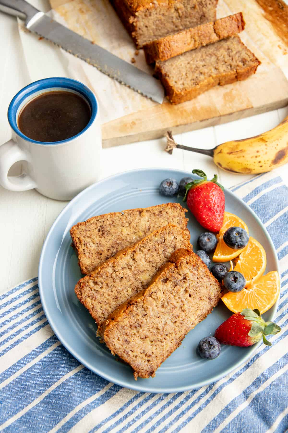 Three slices of paleo banana bread on a blue plate with mixed fruit, next to a cup of coffee.