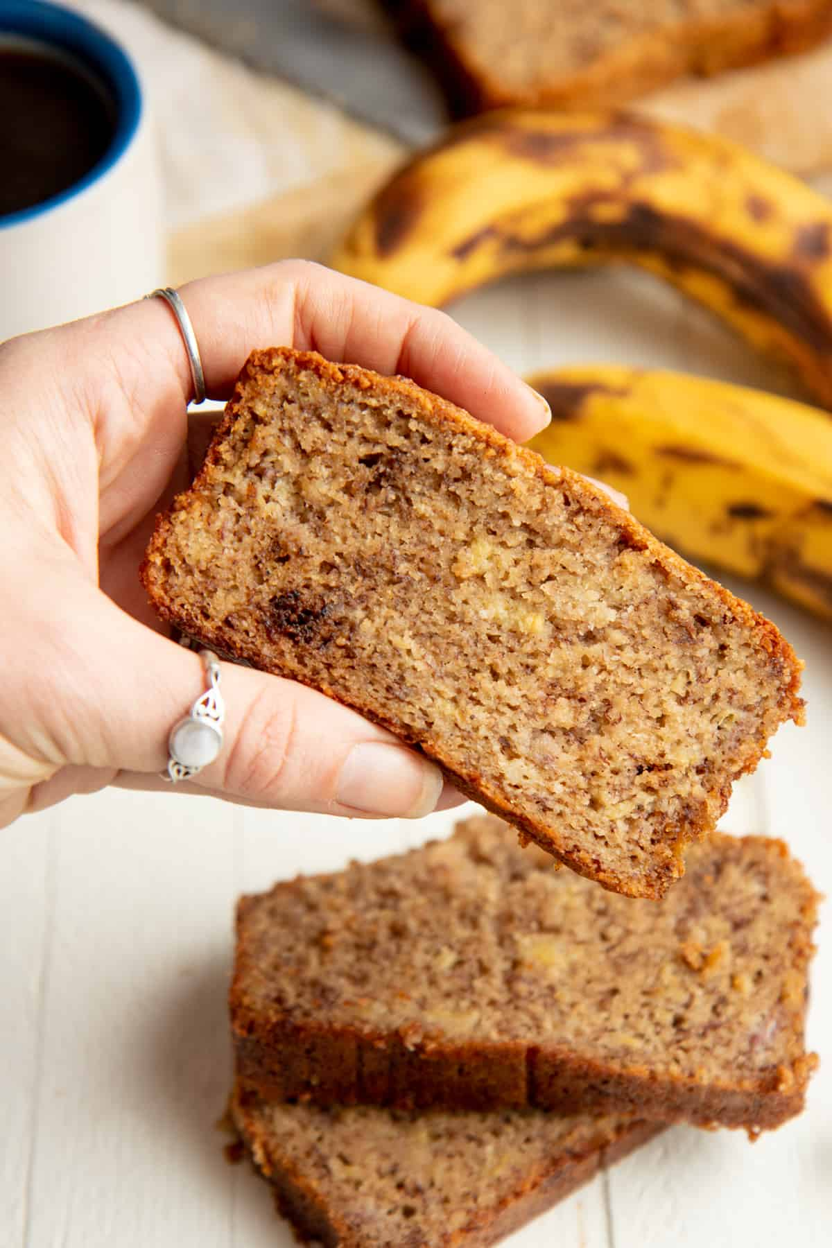 A woman's hand holds a slice of almond flour banana bread over a stack of other slices.