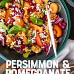 "A fork rests on a dark bowl, filled with persimmon and pomegranate salad. A text overlay reads ""Persimmon & Pomegranate Spinach Salad."""