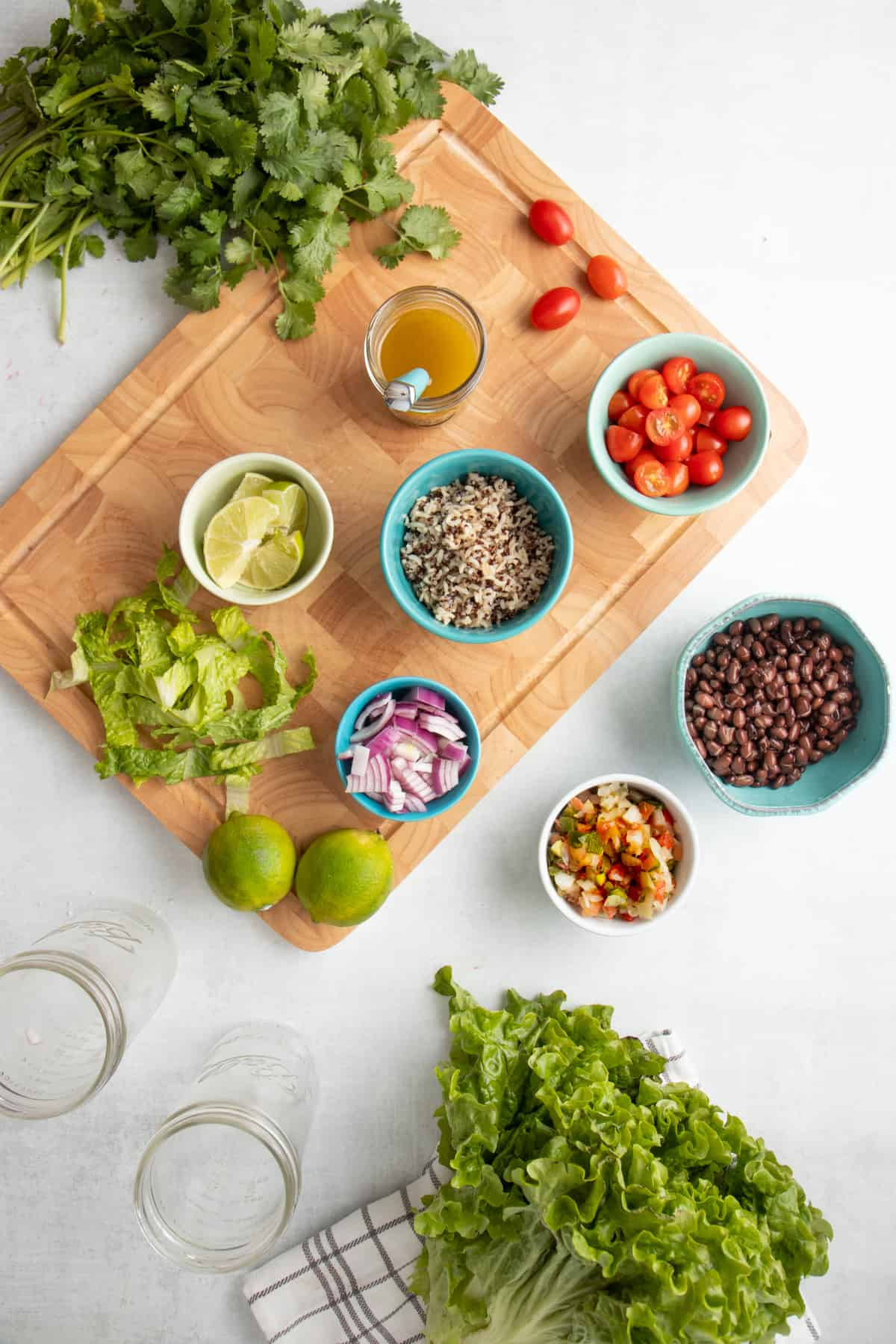 Ingredients for black bean fiesta salad are in blue bowls. Bowls are sitting on a wooden cutting board and a white countertop. Two empty jars and lettuce are on the counter.