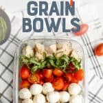 "A glass dish filled with grain bowl ingredients sits on a brown and white dishtowel. Tomatoes and mozzarella sit on the side. A text overlay reads ""Meal Prep Chicken Caprese Grain Bowls."""