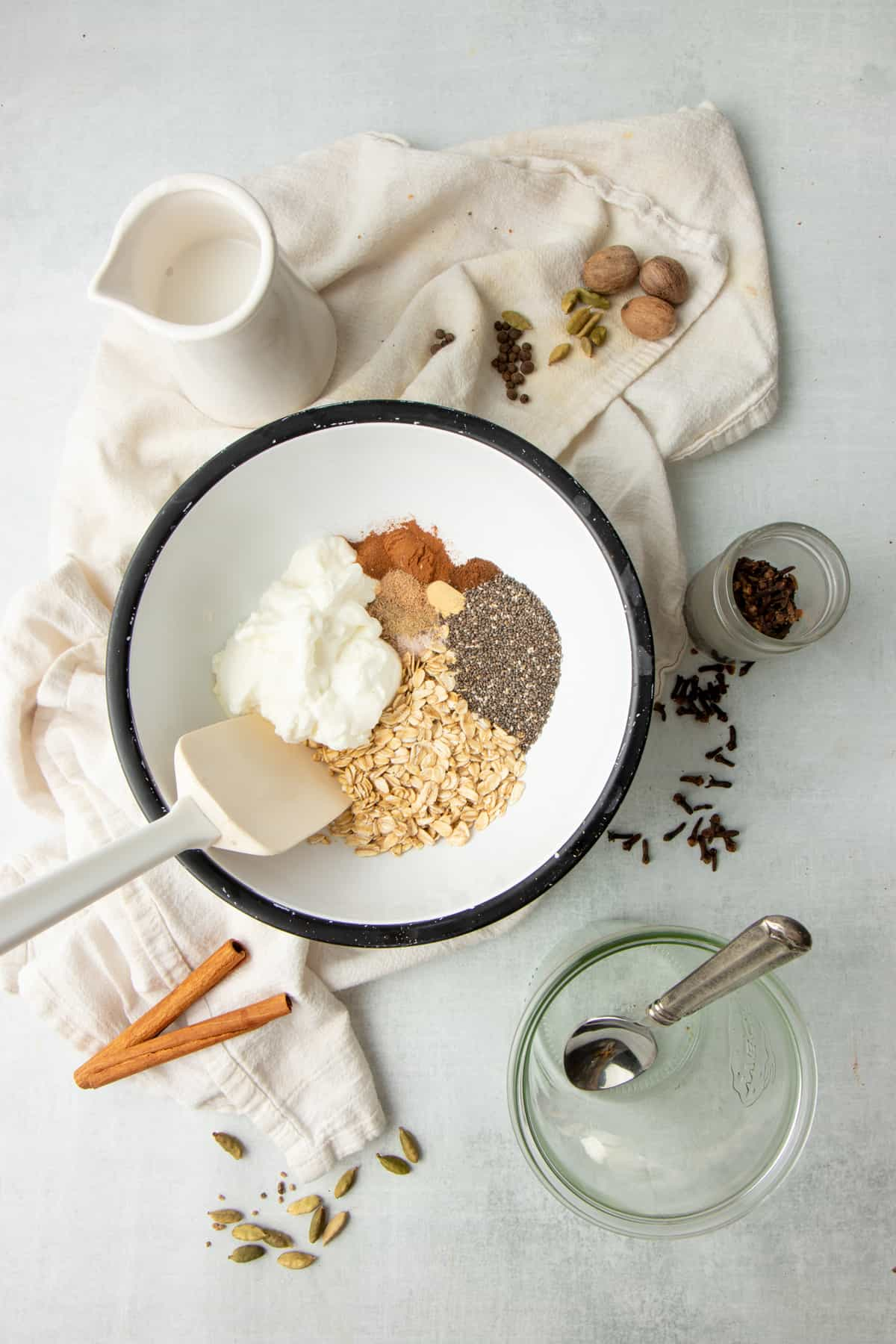 A white rubber spatula sits in a white mixing bowl full of oatmeal, chia seeds, Greek yogurt, and other ingredients.