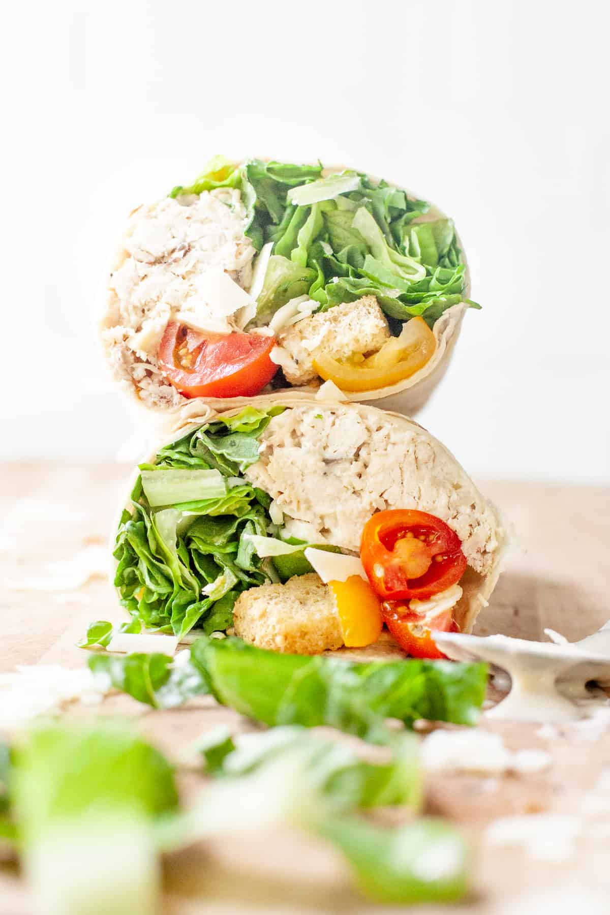 Two halves of easy chicken Caesar wraps are stacked. A spoon with dressing dripping off rests on wooden cutting board.