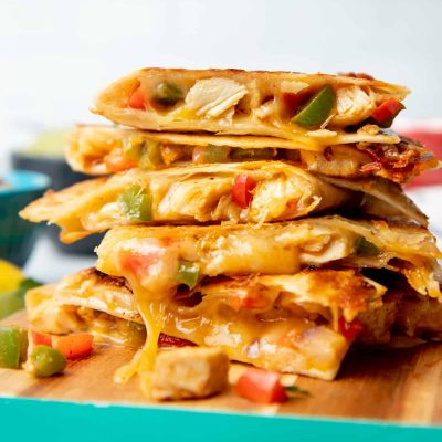 Chicken quesadillas are stacked on top of a wooden cutting board.