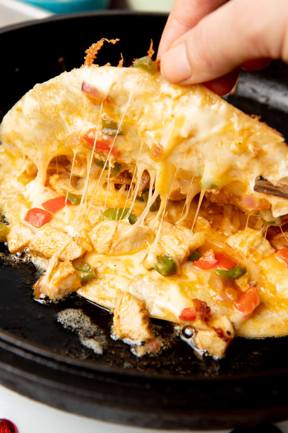 A hand lifts the top of a folded quesadilla. Chicken, peppers, and cheese are inside.