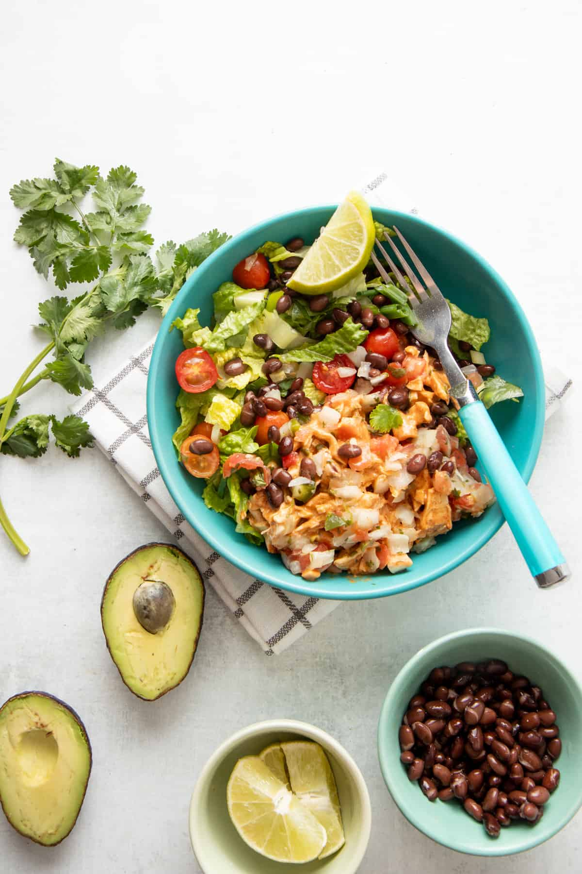 A teal bowl is filled with chicken taco salad. A lime wedge and a fork with an aqua handle rest in the bowl. A halved avpcado rests on a white countertop.