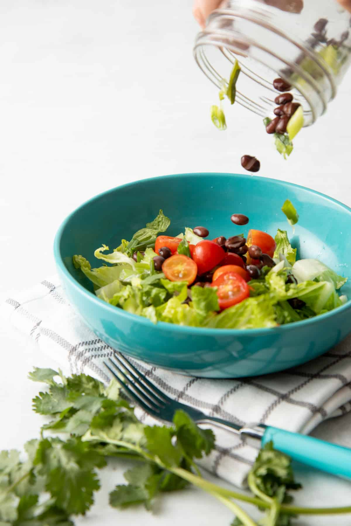 Black beans and lettuce pour out of a jar into a teal bowl. The bowl is filled with lettuce, tomatoes, and black beans.