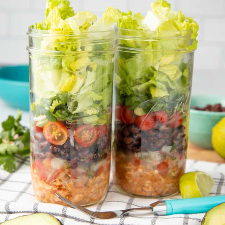 Two mason jars are layered with chicken, black beans, tomatoes, and lettuce. A fork with a teal handle rests in front of the jars.