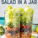 "Two mason jars are layered with chicken, black beans, tomatoes, and lettuce. A fork with a teal handle rests in front of the jars. A text overlay reads ""Chicken Taco Salad in a Jar."""
