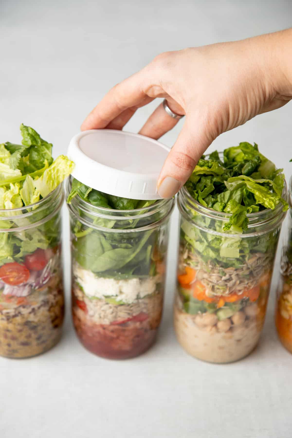 Three tall mason jars are layered with salad ingredients. A hand places a white lid on the middle jar.
