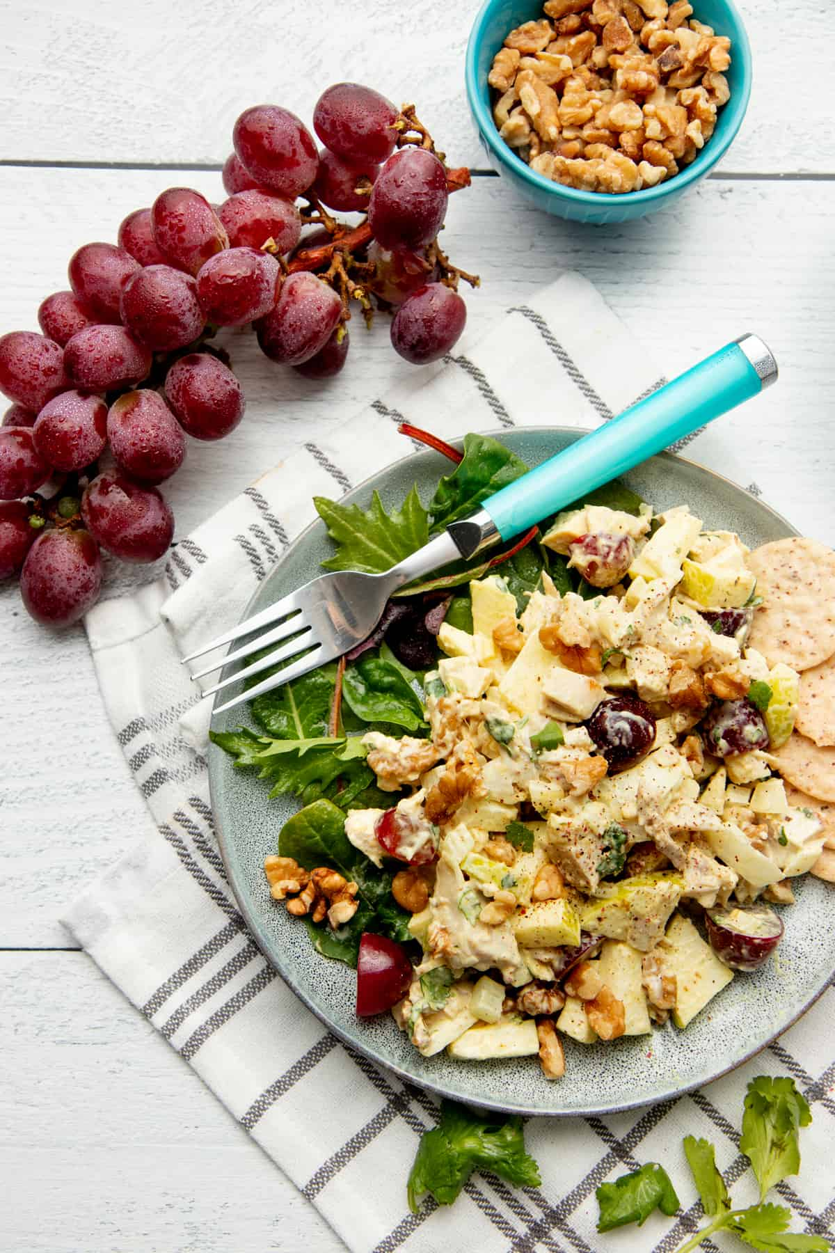 A gray plate holds chicken salad and lettuces. A blue fork rests on the plate. Red grapes also sit on a white wooden counter.