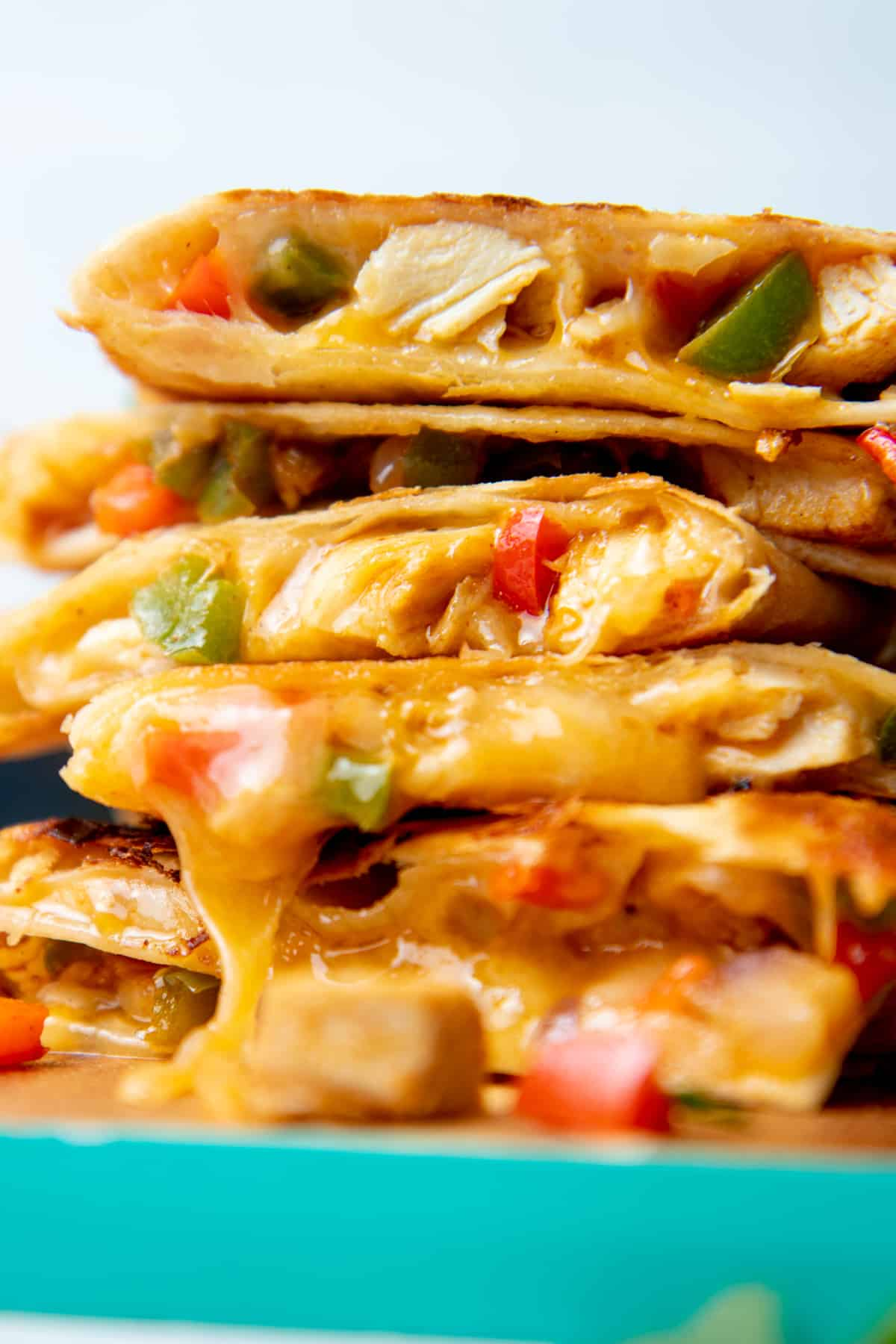 Stack of quesadilla slices filled with chicken, peppers, and cheese. The stack sits on a teal-edged cutting board.
