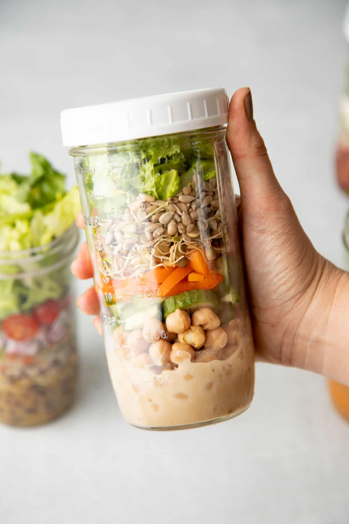 A hand holds a tall mason jar with a white lid. Jar is layered with salad ingredients, including dressing, chickpeas, vegetables, seeds, and lettuce.