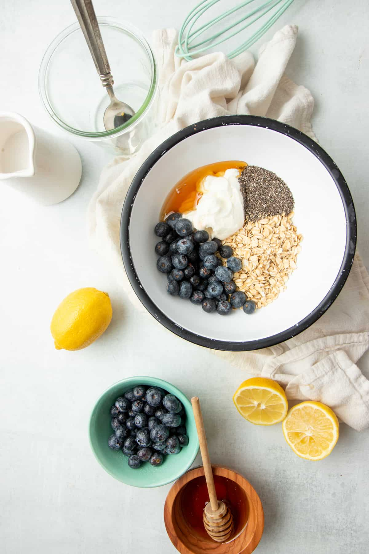 A mixing bowl filled with blueberries, oats, Greek yogurt, chia seeds, and other ingredients sits next to a halved lemon.