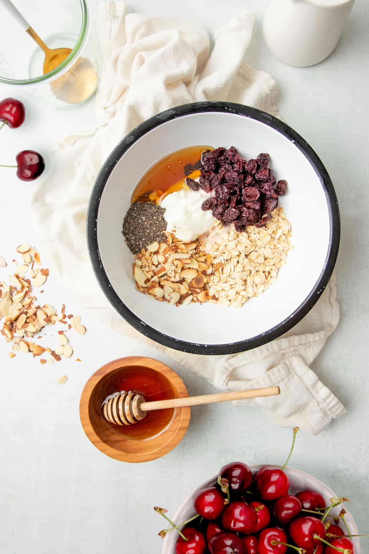 White mixing bowl full of ingredients such as oats, Greek yogurt, chia seeds, dried cherries, and more.