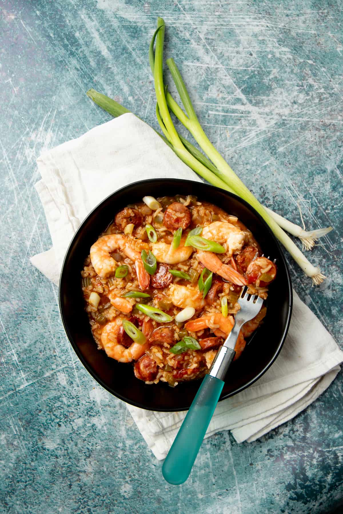 A piece of sausage rests on a fork inside a bowl of jambalaya. Whole green onions lay alongside the bowl.