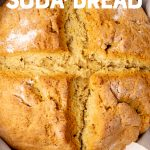 """A round loaf of Irish soda bread rests in a cast iron skillet. Text overlay reads, """"easy Irish soda bread."""""""