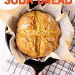 "A round loaf of Irish soda bread rests in a cast iron skillet. A hand holds the handle of the pan. Text overlay reads, ""easy Irish soda bread."""