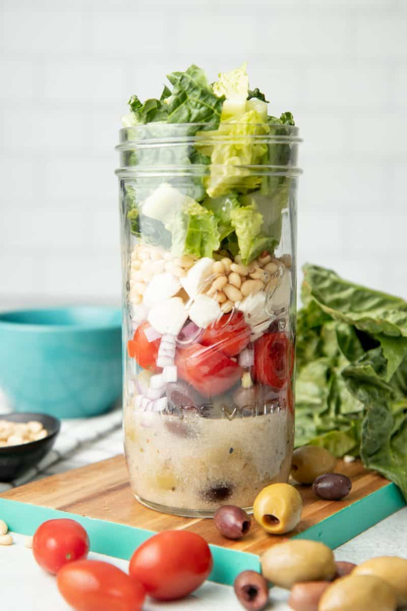 A mason jar salad sits on a teal-edged cutting board, surrounded by lettuce, olives, and cherry tomatoes.