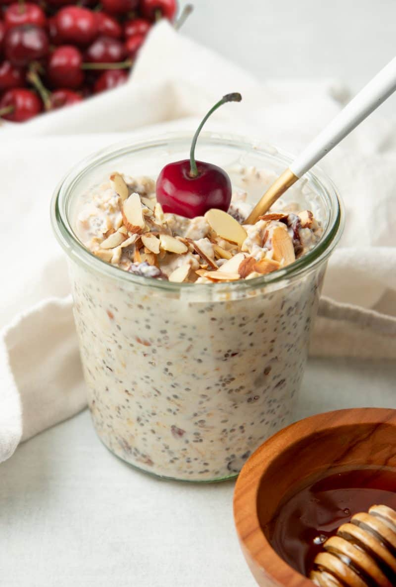 A spoon rests in a glass jar of cherry and almond overnight oats. The oats are garnished with a whole fresh cherry.