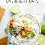 """A spoon with a blue handle sits in a jar of key lime pie overnight oats. A text overlay reads, """"Key Lime Pie Overnight Oats."""""""