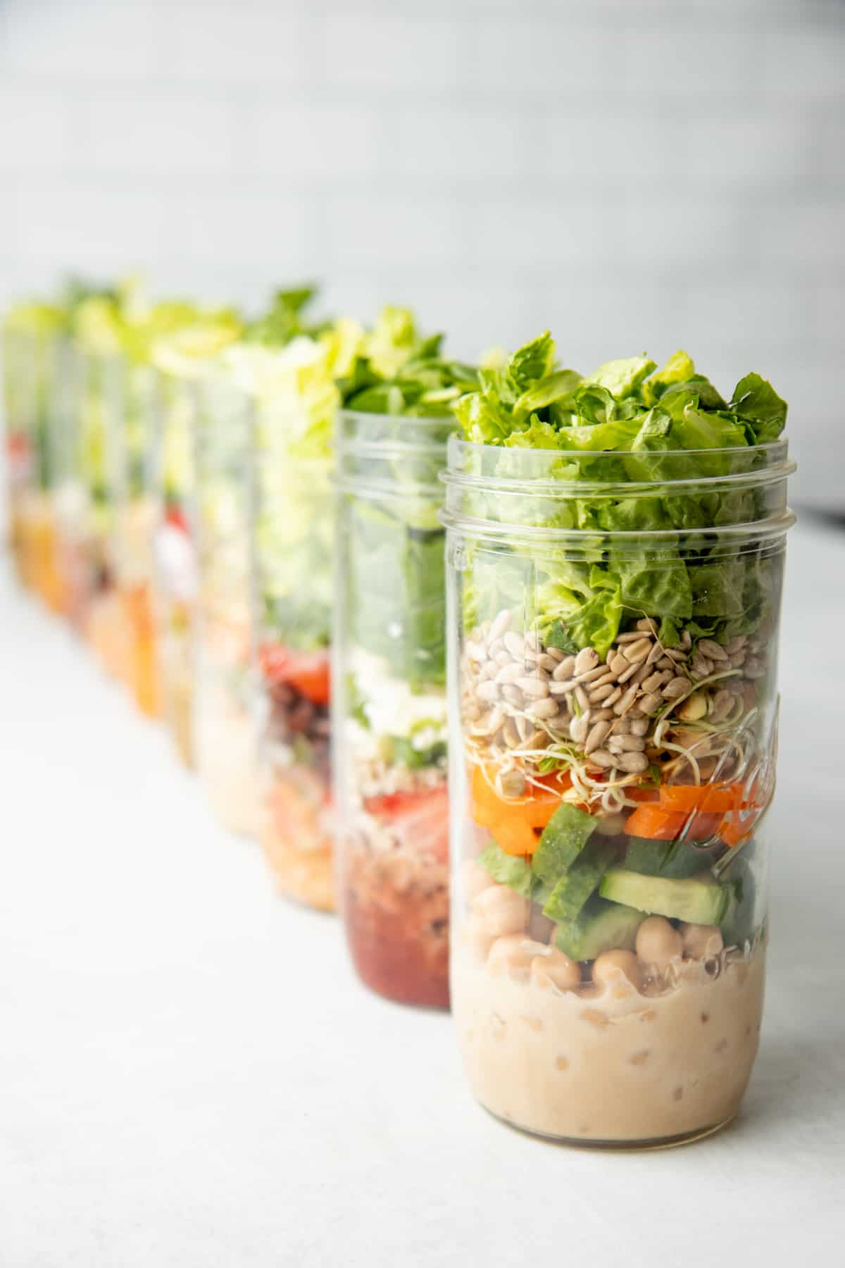 Ten tall mason jars are layered with salad ingredients.