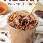 "A gold spoon sits in a jar full of mocha overnight oats. A text overlay reads ""Mocha Overnight Oats."""