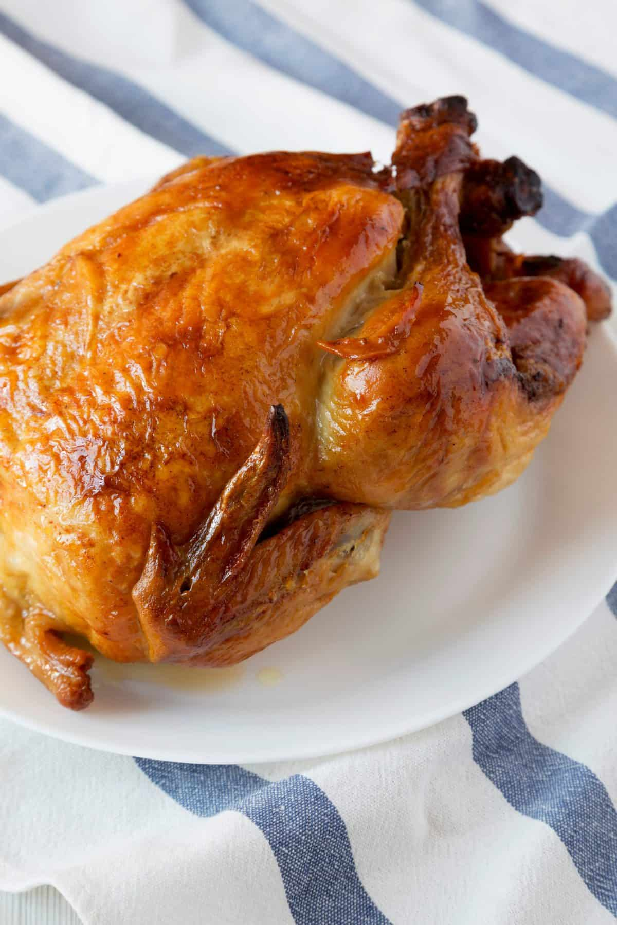 A rotisserie chicken sits on a white plate. The plate sits on a blue and white striped cloth.