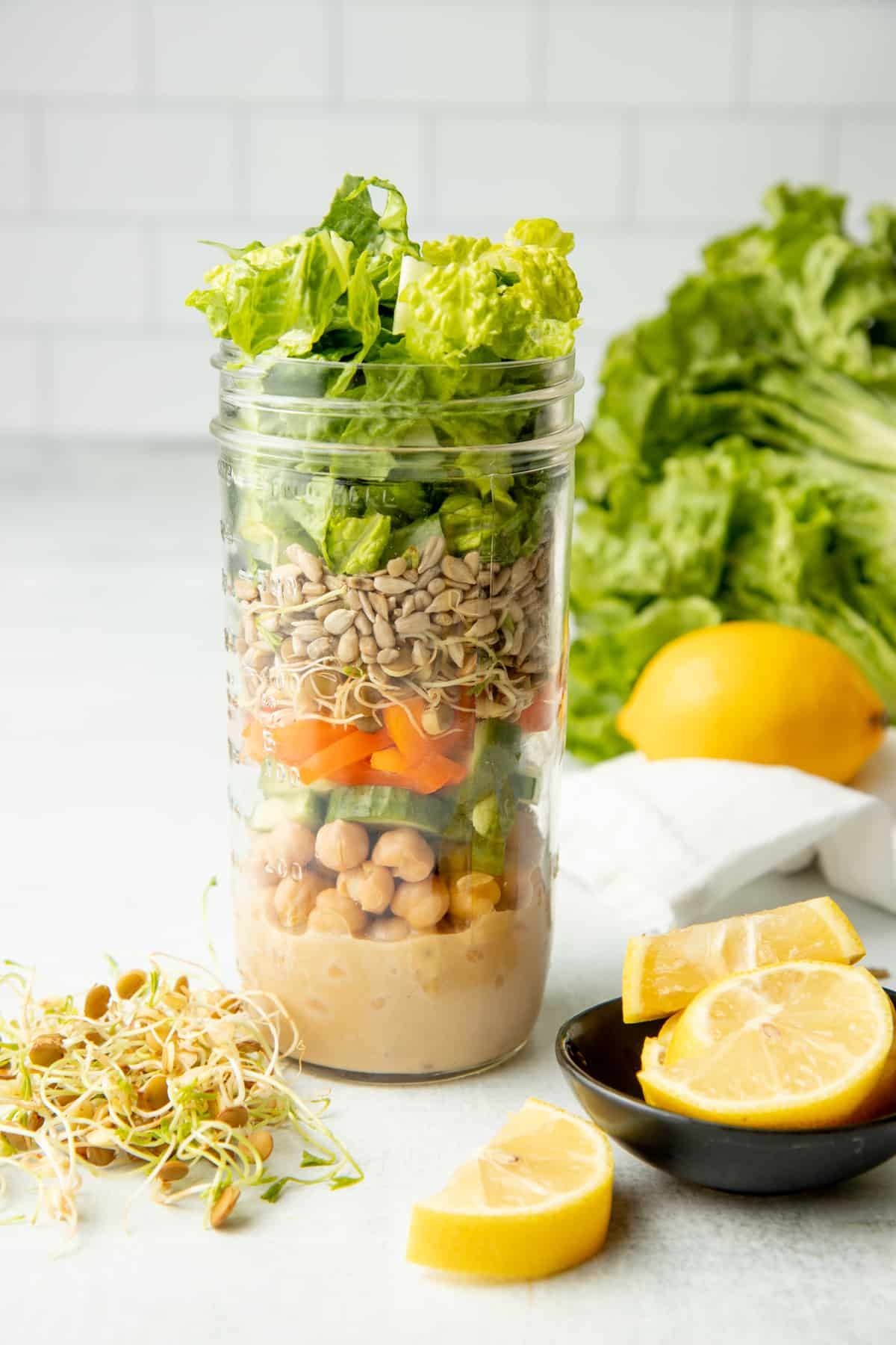 Glass mason jar filled with layers of components for a sesame chickpea salad, surrounded by extra ingredients.