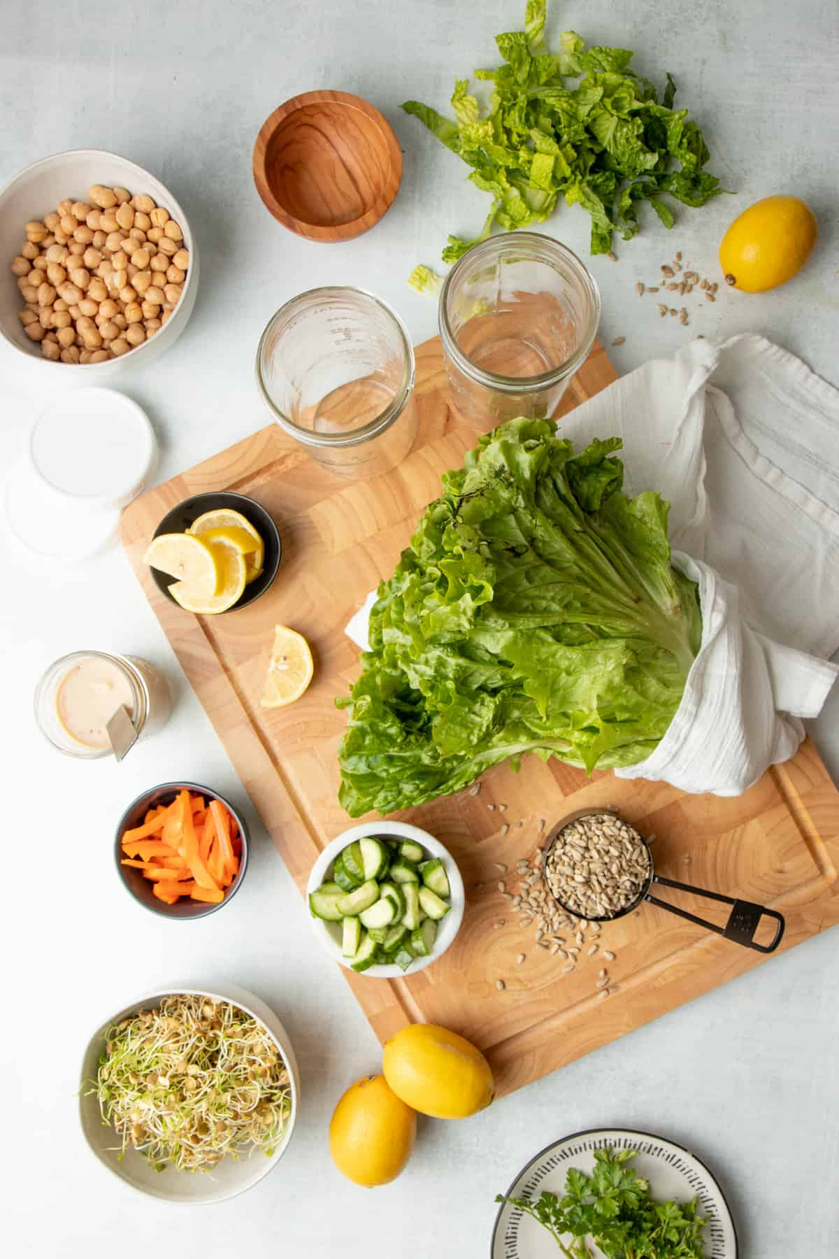Two empty glass jars, lettuce, and sliced lemons sit on a wooden cutting board. Around the board, chickpeas, sprouts, and other ingredients sit on a white countertop.