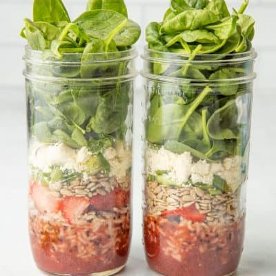 Two mason jars sit side-by-side, layered with components of strawberry spinach salads.