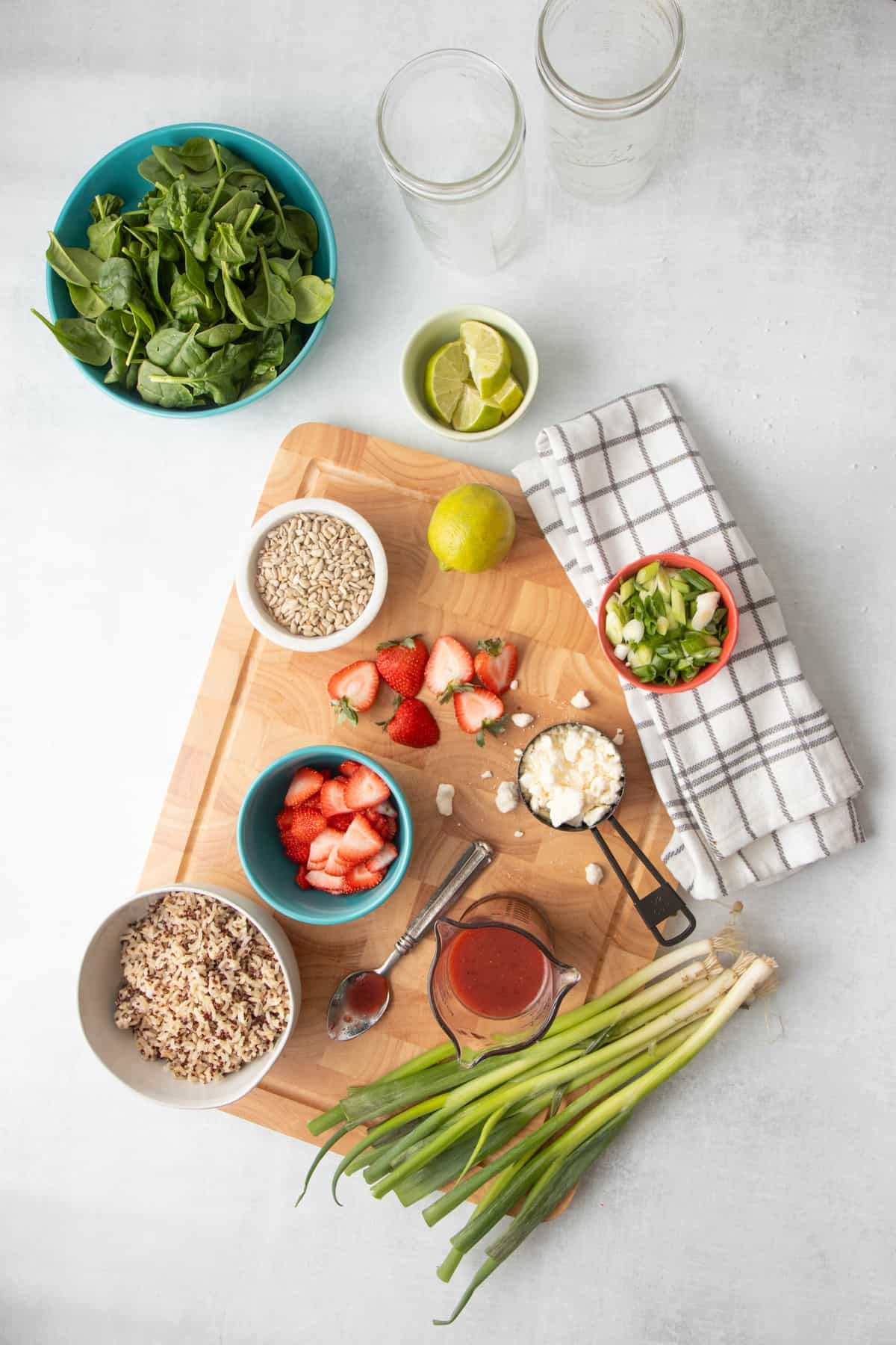 Ingredients for a strawberry spinach salad laid out in individual containers - strawberries, feta, green onions, spinach, lime slices, vinaigrette, and grains.