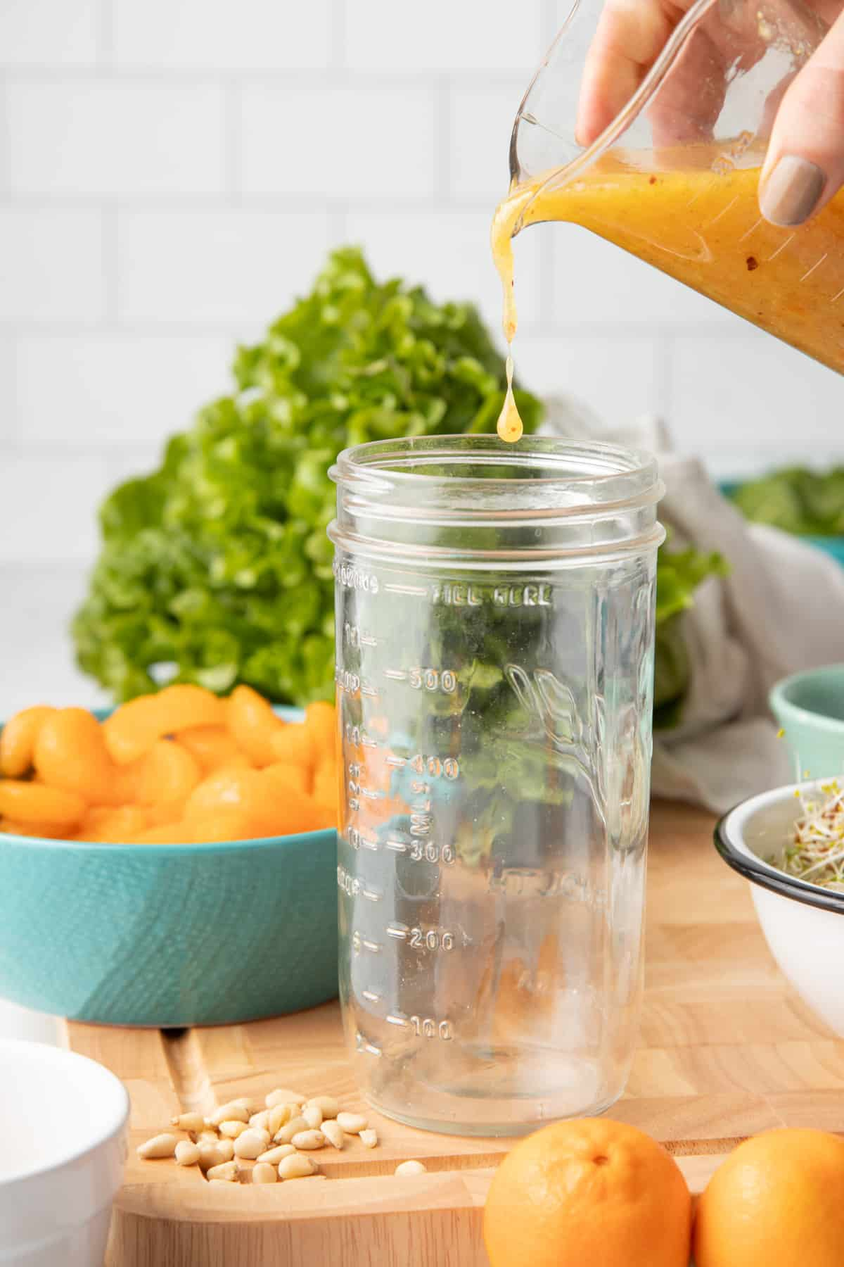 A hand pours orange marmalade vinaigrette from a measuring cup into the bottom of a mason jar.