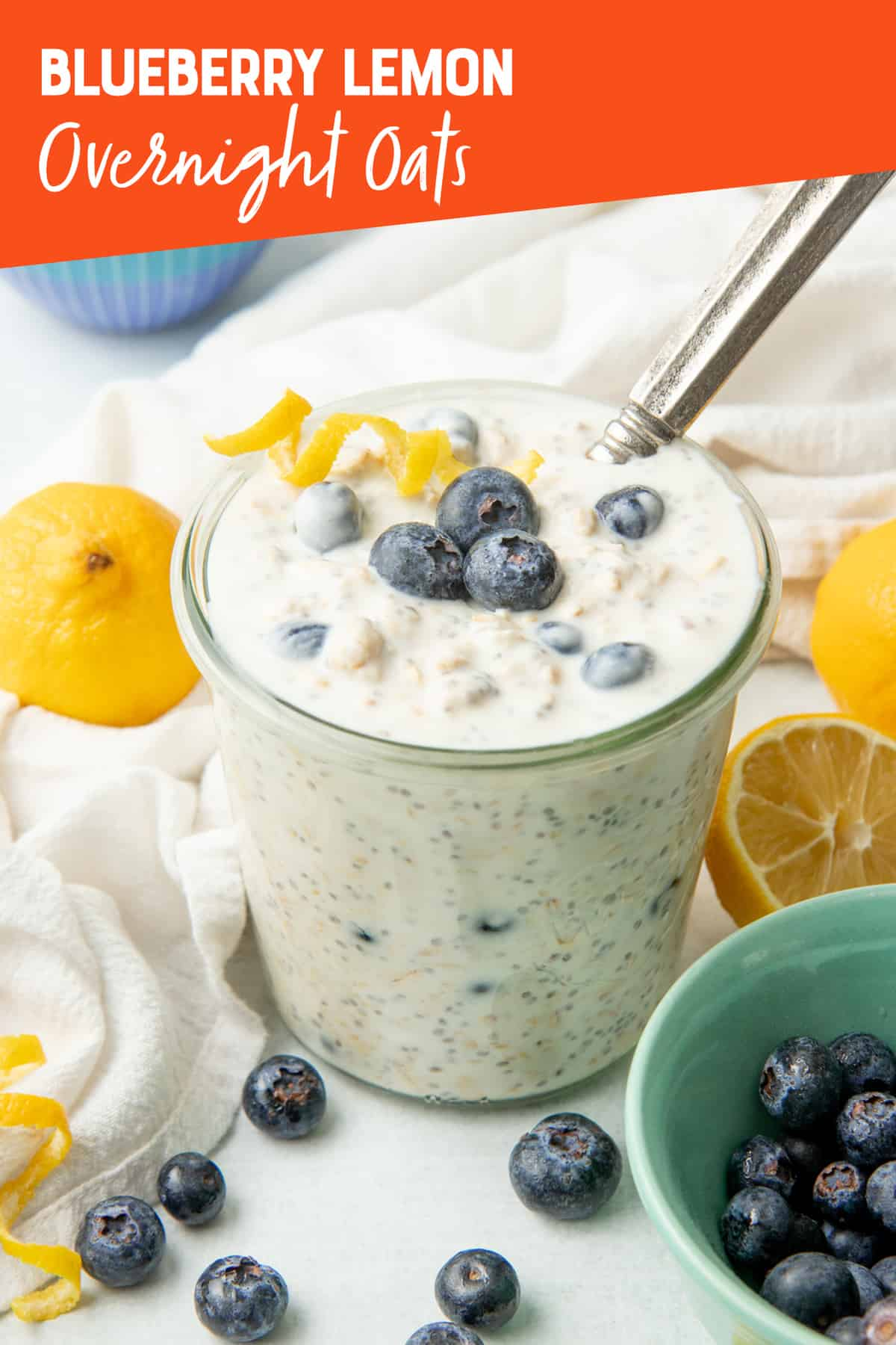 A spoon sits in a jar of blueberry overnight oats. Lemons surround the jar.