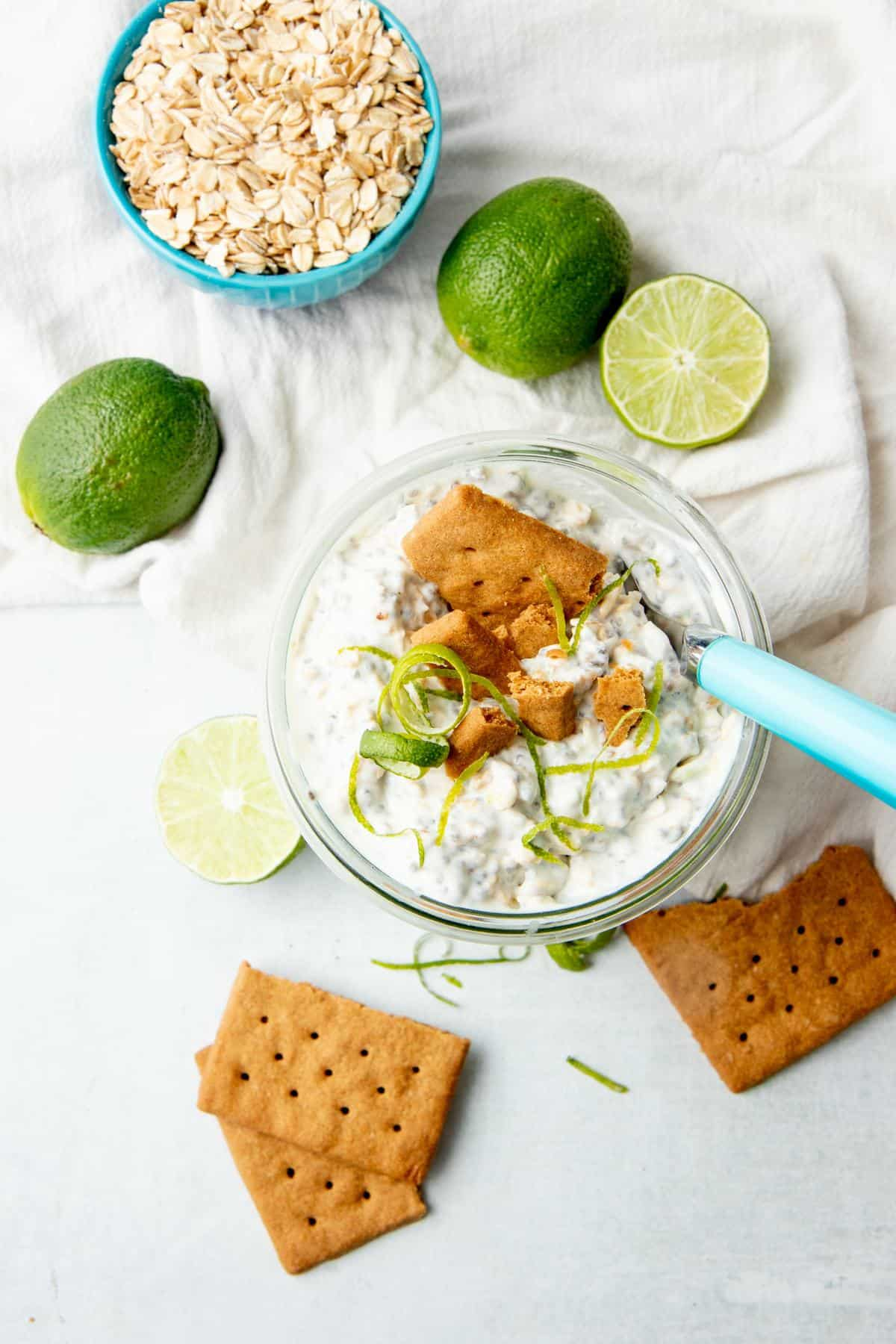 A spoon with a blue handle sits in a jar of overnight oats. Limes and graham crackers surround the jar.
