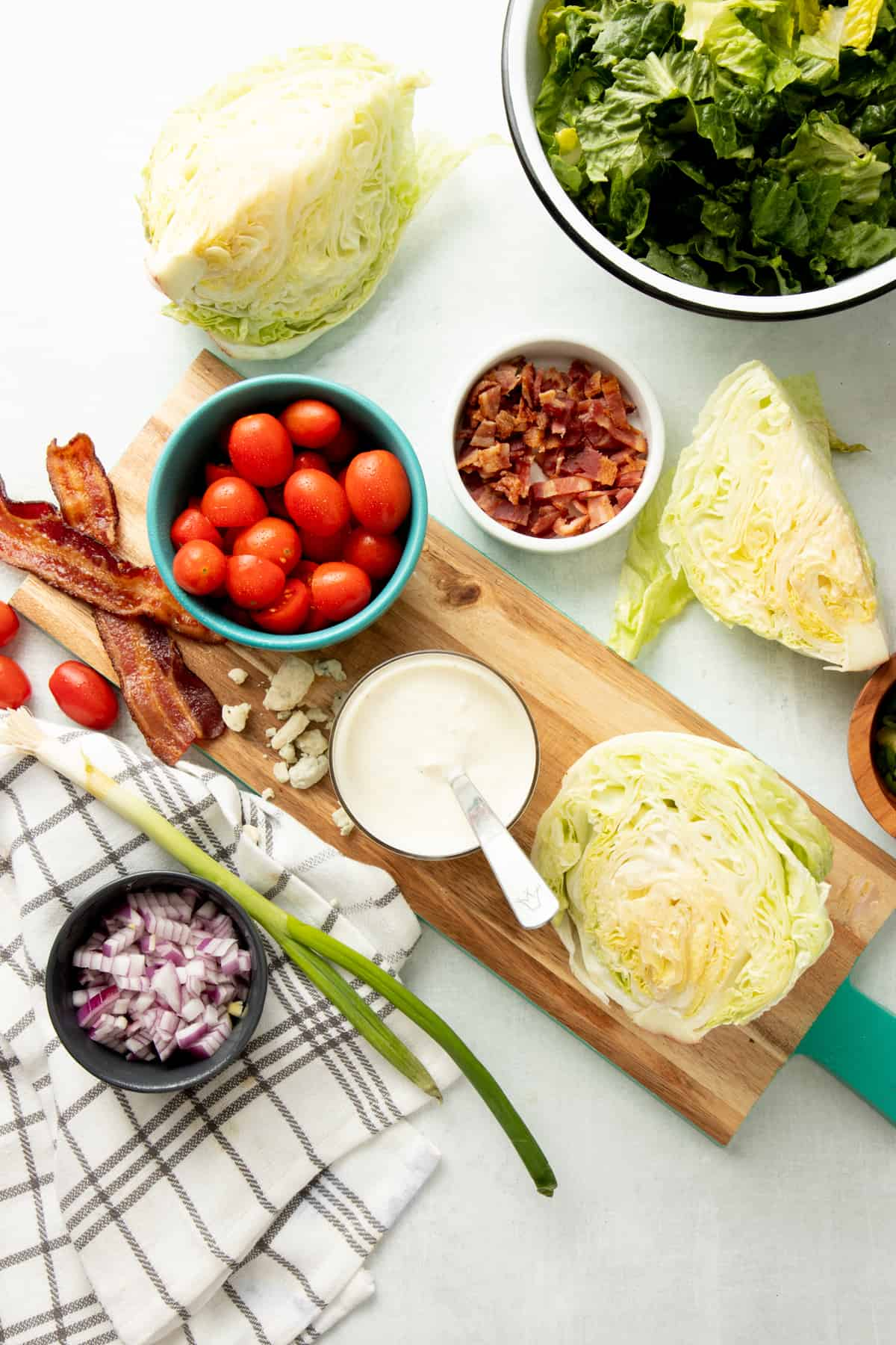 Ingredients for a wedge salad are laid out on a white counter, wooden cutting board, and plaid dish towel.