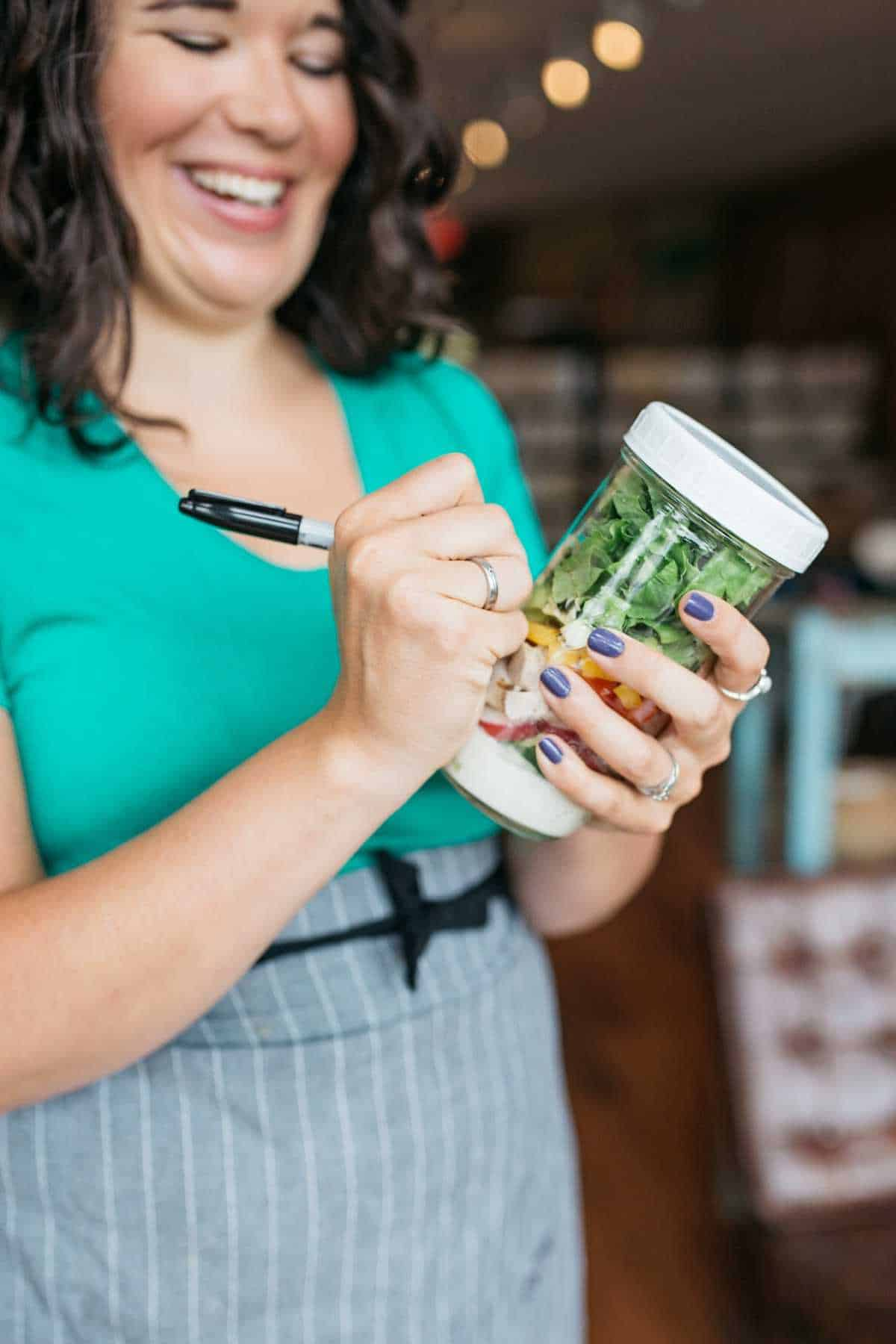 Smiling woman in teal shirt and gray apron uses a permanent marker to write on a jar filled with salad ingredients.
