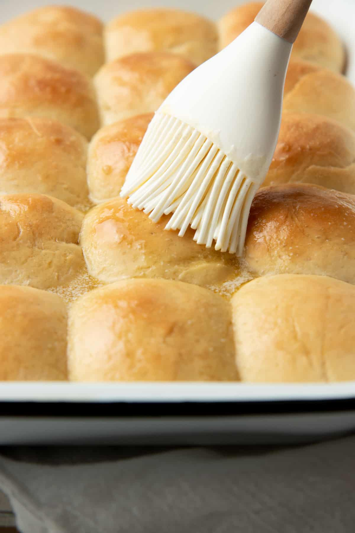 A brush brushes butter on a pan of freshly baked rolls.