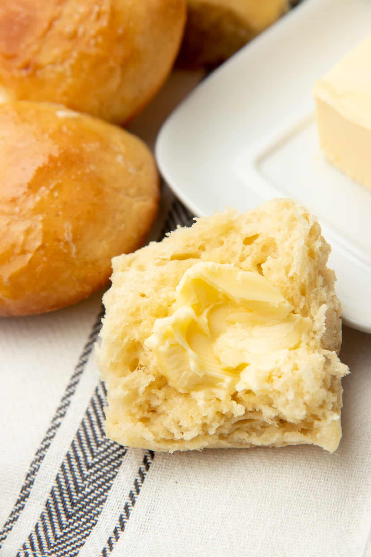 A bread roll cut in half is spread with butter and sits on a towel.
