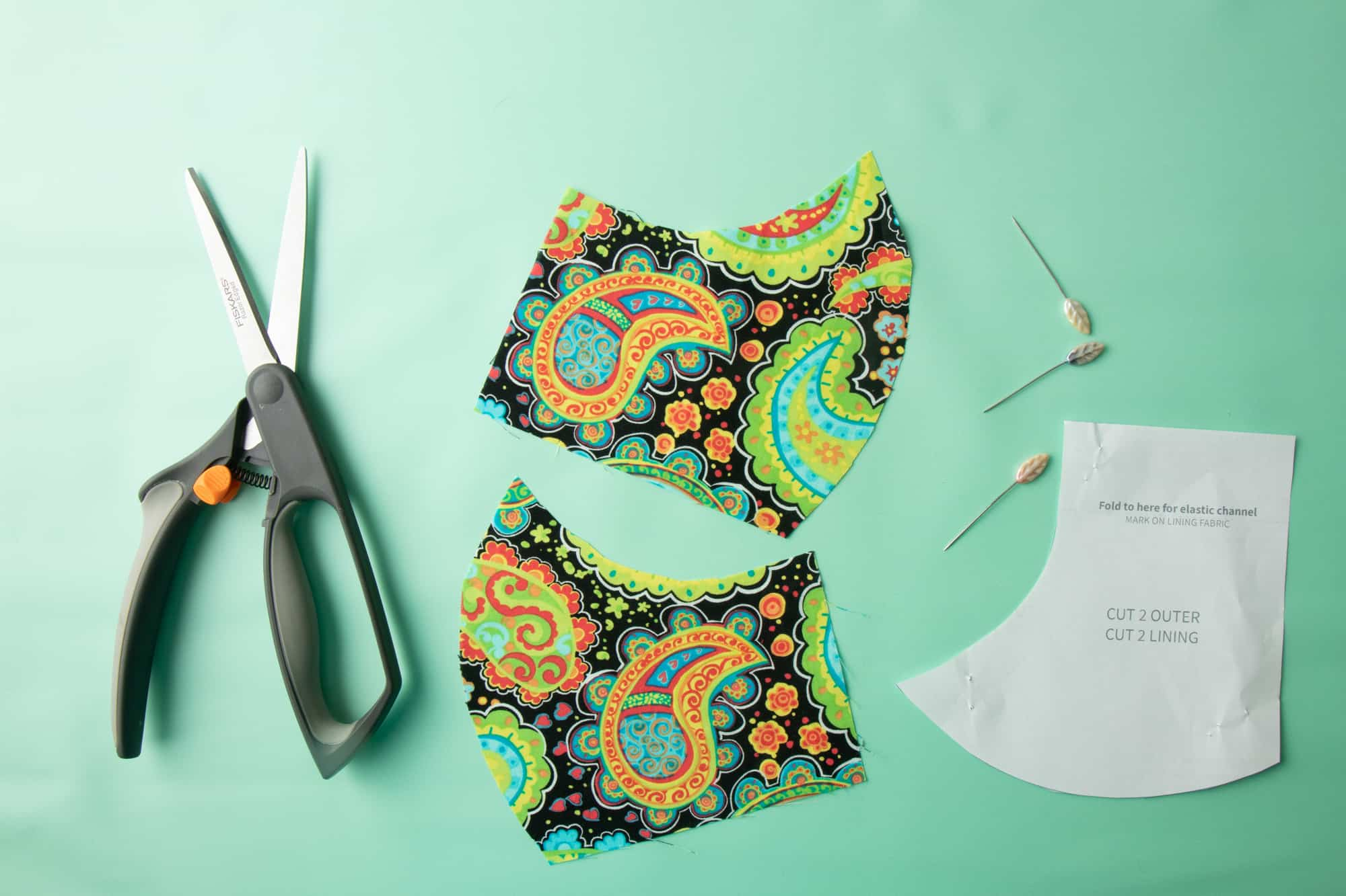 Scissors sit next to cut out fabric pieces, paper pattern pieces, and pins.