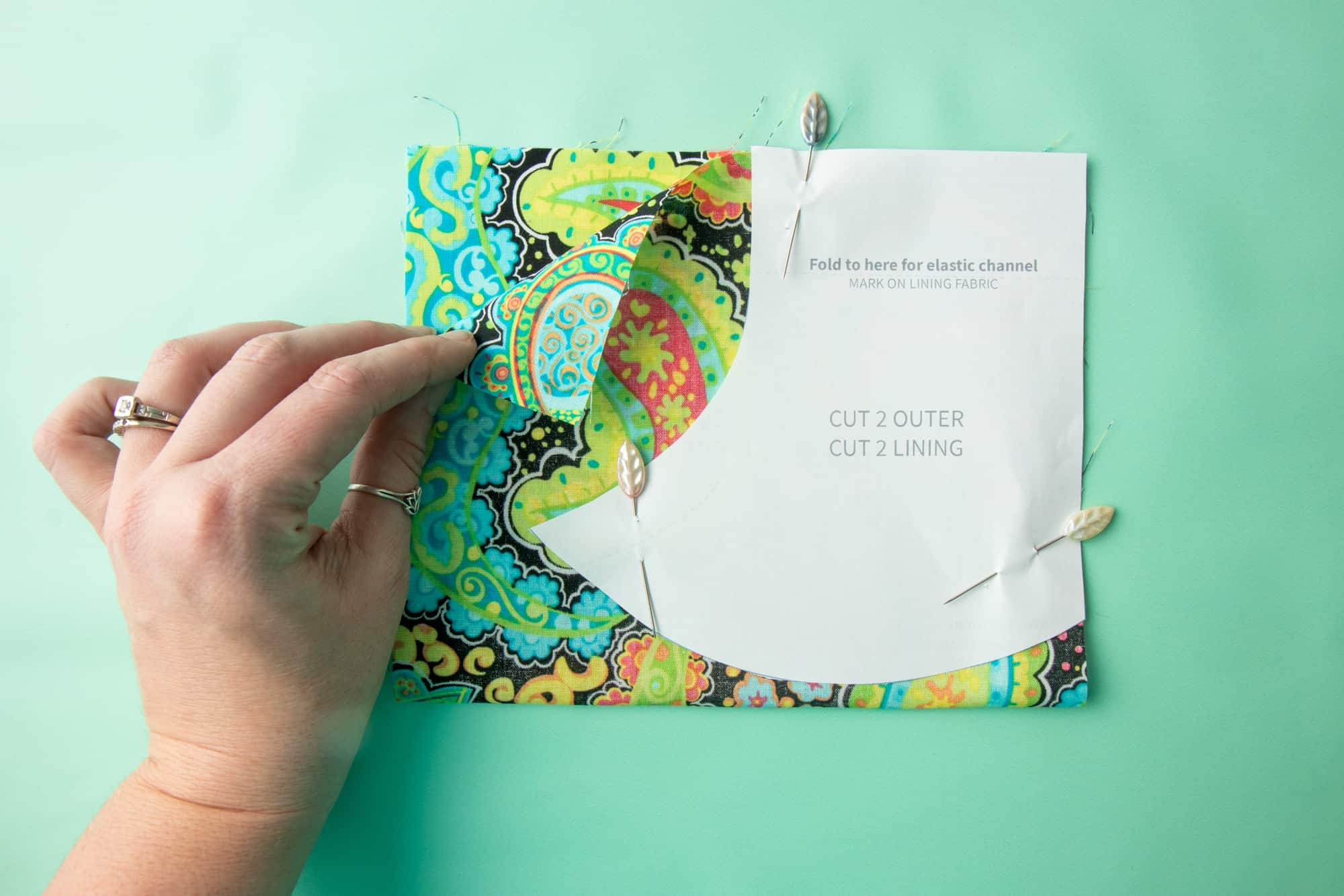 The paper pattern sits on top of the fabric, pinned, on a green background. A hand holds it in place.
