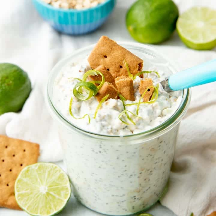 A small glass jar is filled with overnight oats and topped with graham cracker and lime twists.