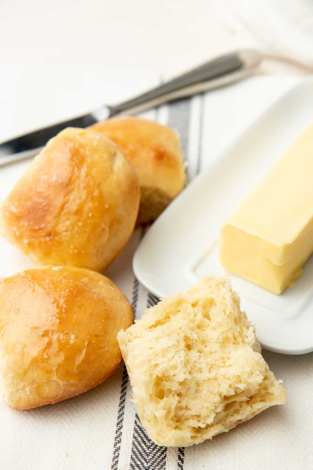 A cut roll sits next to whole rolls and a dish of butter.