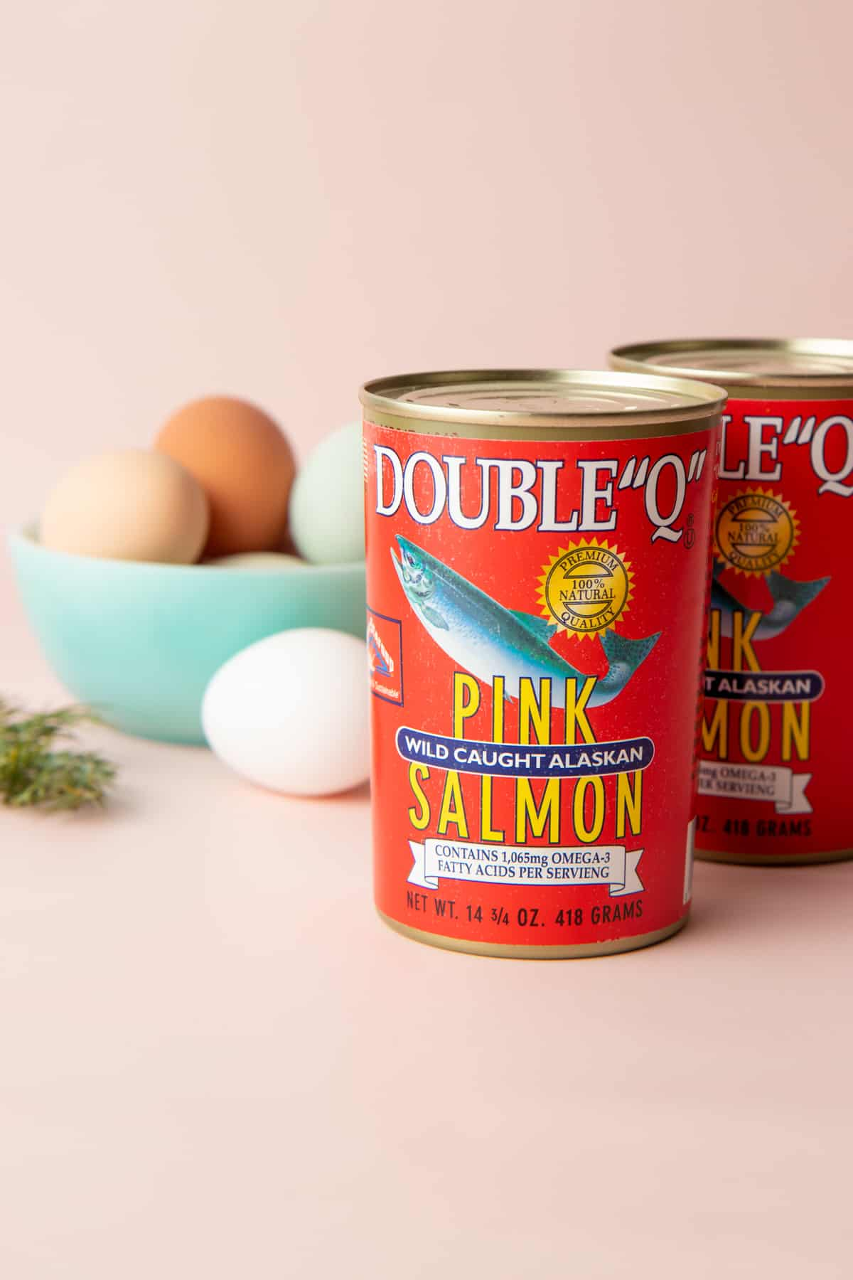 Two cans of Double Q Pink Salmon sit in front of a bowl of eggs.