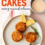 "A plate of salmon cakes, lemon, and a sprig of dill sit on a plate. A bowl of Remoulade sauce sits nearby. A text overlay reads ""salmon cakes using canned salmon"""