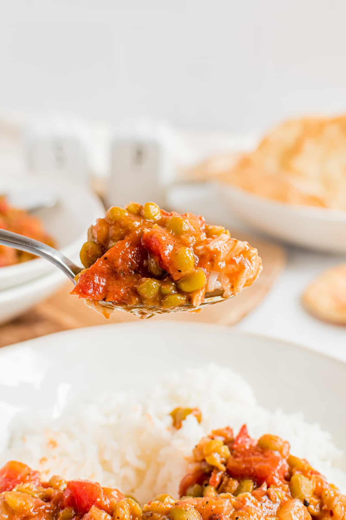 A spoon holds a bite full of Split Pea Curry.