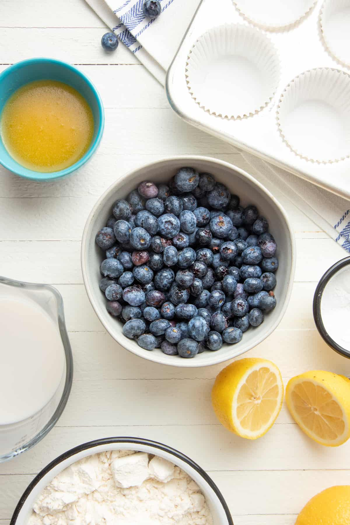 Blueberries sit in a bowl. A muffin pan, lemon slices, and other ingredients sit to the side.