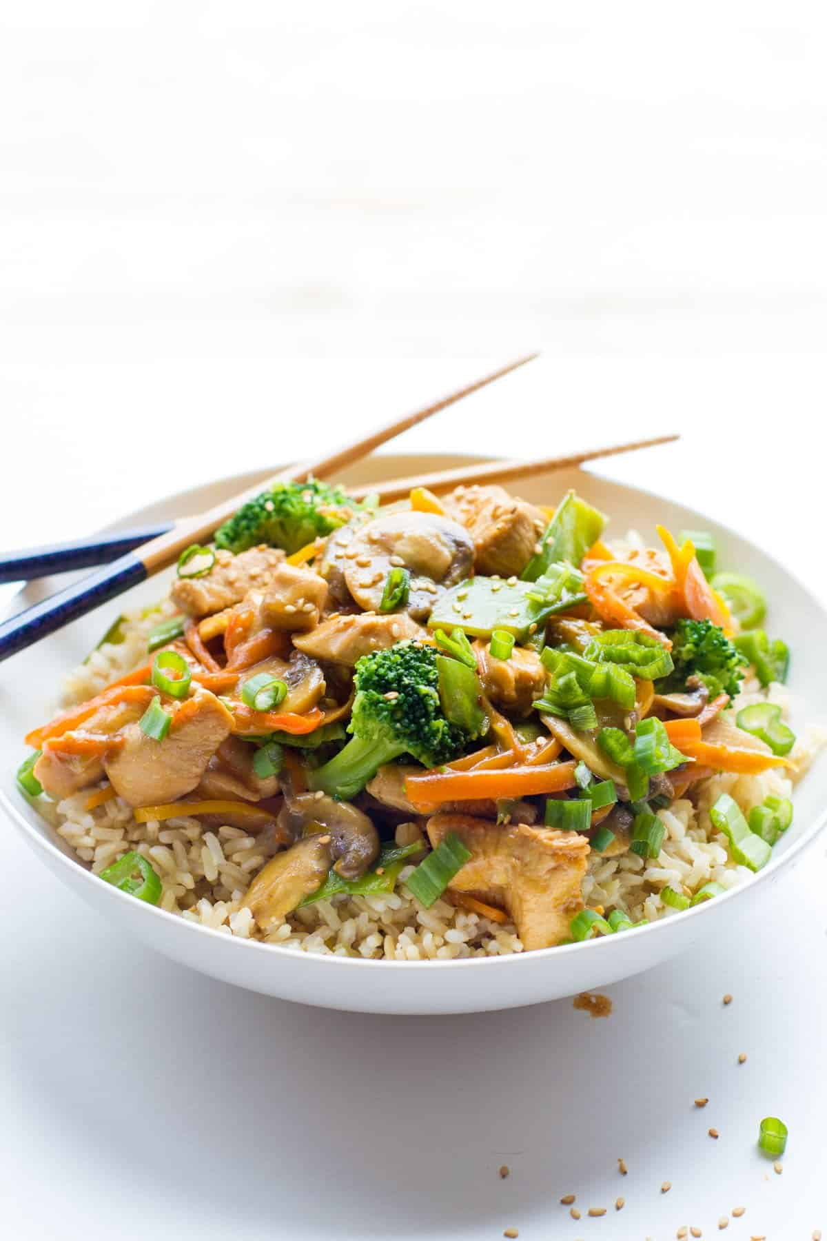 Healthy Chicken Stir Fry sits in a bowl with chopsticks.
